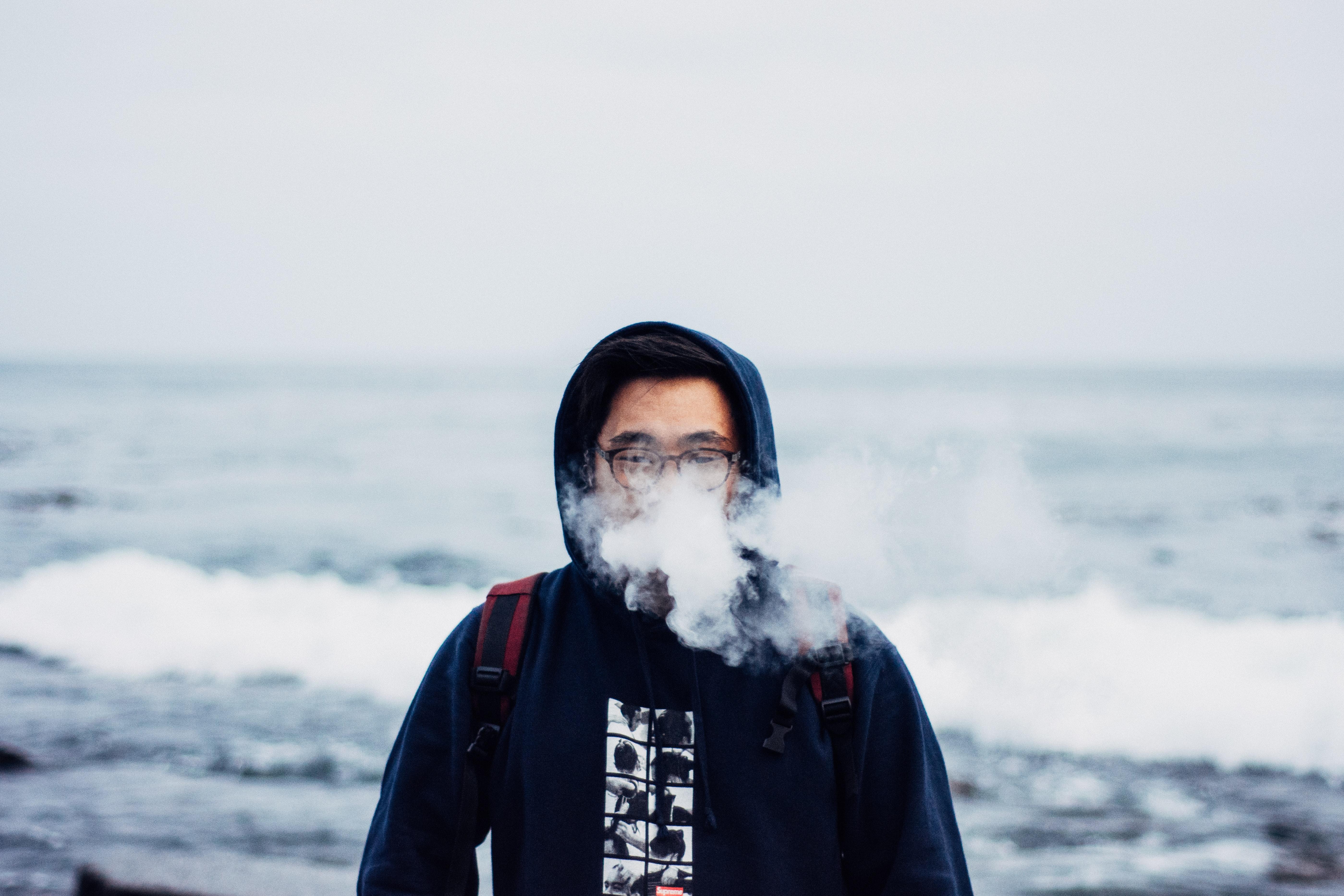 person in black hoodie smoking