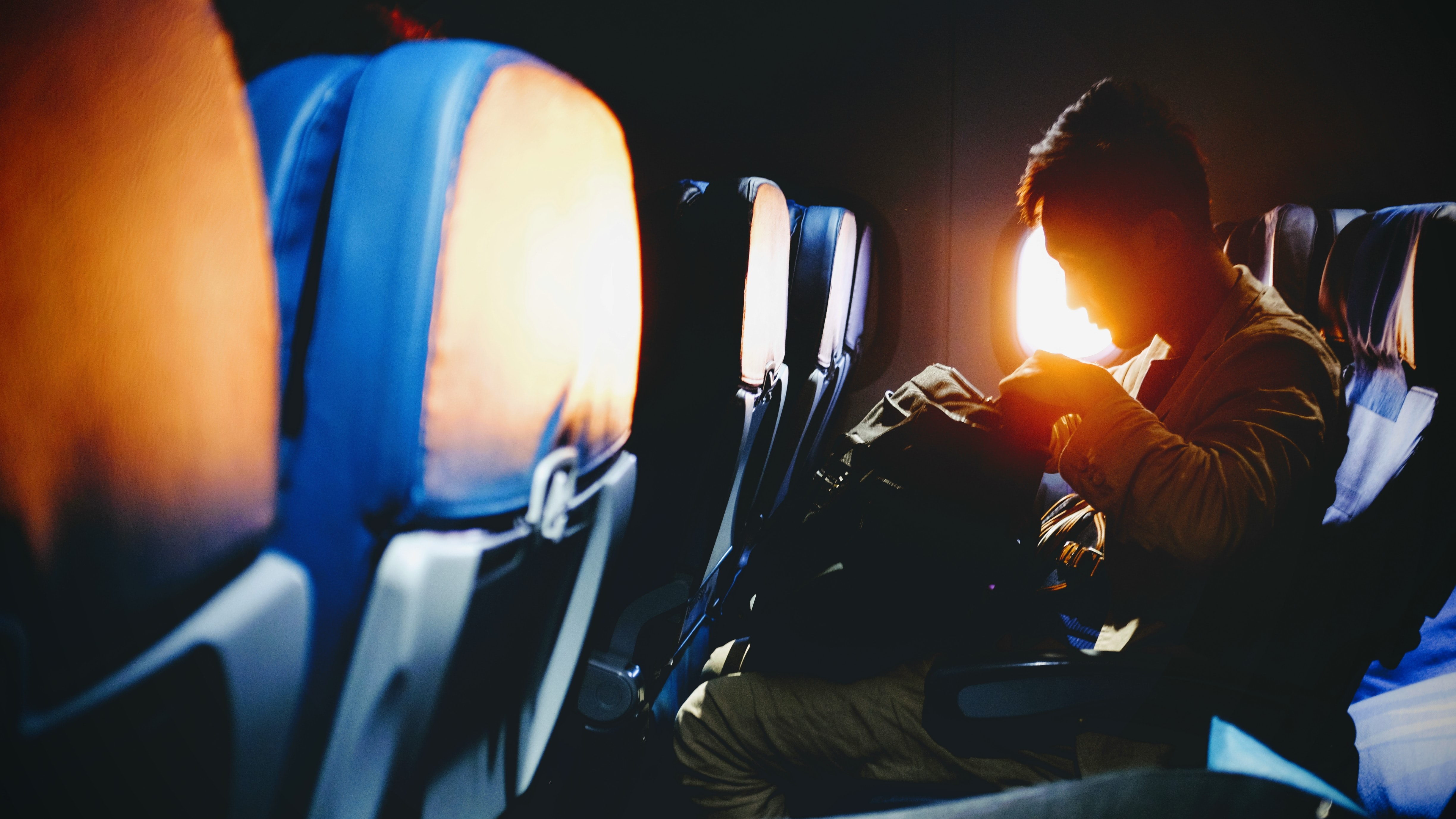 man looking on his sitting on plane seat
